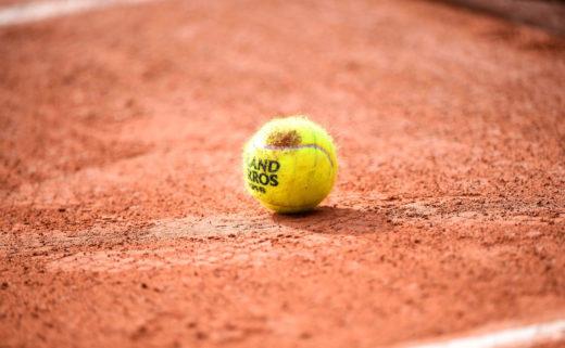 Balle de tennis de Roland Garros déposée au sol sur de la terre battue.