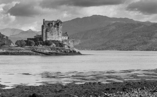 Photo en Noir et Blanc effectuée par Sarkis Ohanessian. Elle représente un château d'Écosse entouré d'un loch.