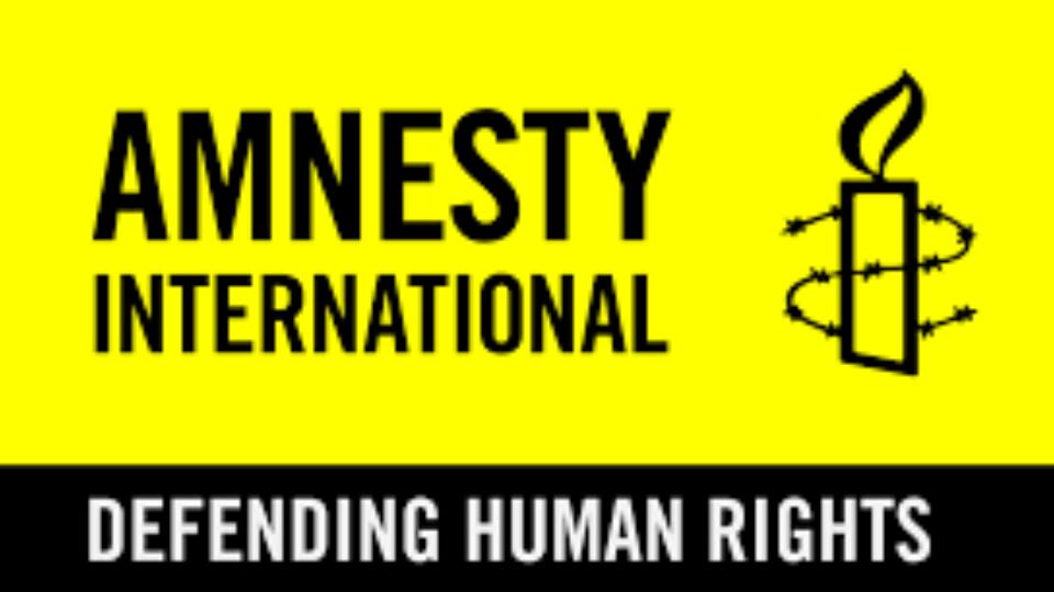 """Logo officiel d'Amnesty International, sur lequel est dessinée une bougie entourée de barbelé et il est écrit en dessous """"defending human rights""""."""
