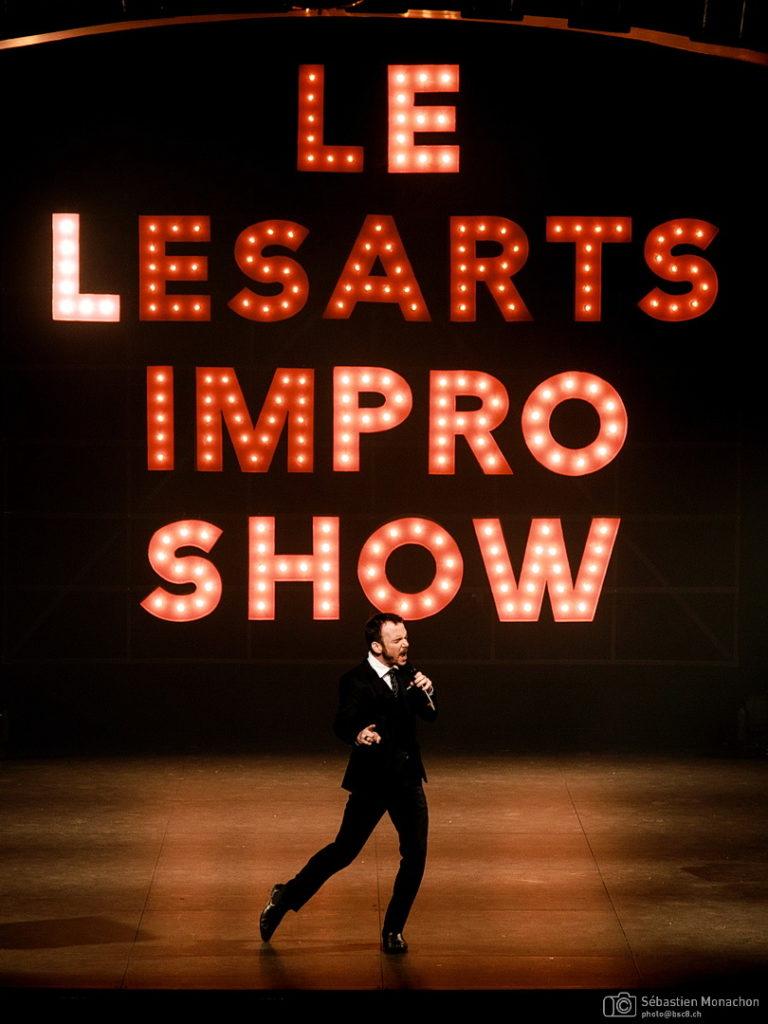"""Sarkis Ohanessian, très classe, vêtu d'un costume noir, d'une chemise blanche et d'une cravate noire, est sur la scène du Casino Théâtre de Genève et met le feu au public. Derrière lui, en fond de scène, des panneaux lumineux écrivent """"Le lésants Impro Show"""""""