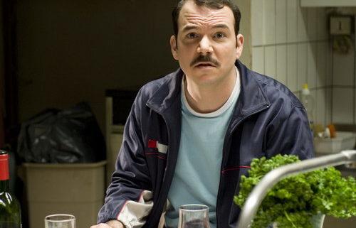 Sarkis Ohanessian, sur le tournage d'Opération Casablanca, joue Gilbert. Il porte une moustache, un pull bleu clair et une veste de training bleu foncé. Il est assis à table avec un verre de rouge devant lui et regard l'objectif d'un air un peu hébété.
