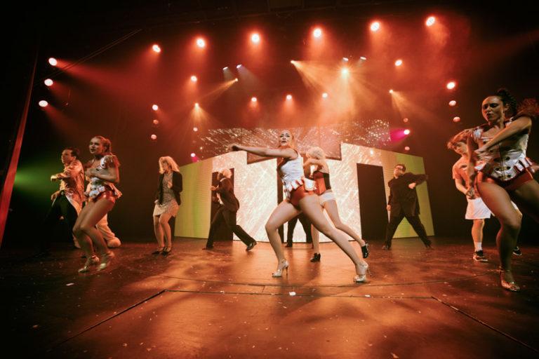 Dans un décor de lumières rouges, les danseurs de la Grande Revue improvisées sont en pleine action