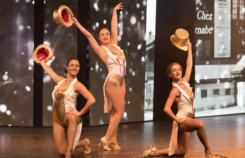 Clarissa Crivelli, Loren Muñoz et Célia Olive, danseuses dans la Grande Revue Improvisée de Servion, sont habillées en doré et effectuent la pose finale d'une chanson en tendant leur chapeau doré vers le haut.