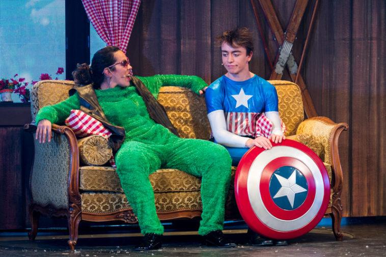 Florence Wavre et Dorian Sönmez, deux comédiens de la Grande Revue Improvisée de Servion, sont assis sur scène dans un canapé. Dorian porte un costume de super-héros et tient un bouclier dans les mains. Florence est dans une sorte de pyjama vert de mauvais goût.