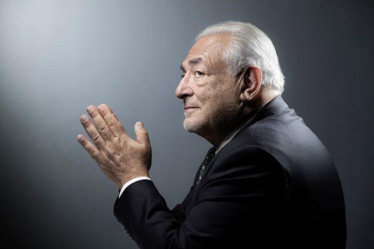 Dominique Strauss-Kahn est de profil, les mains jointes. Il porte un costume noir.