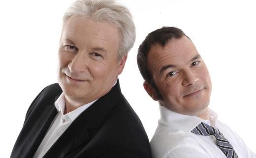 Sarkis Ohanessian et Philippe Robin, animateurs du Grand Quiz et son bêtisier 2009 à la Radio Télévision Suisse. Sarkis porte une chemise blanche et une cravate lignée de noir et gris. Les deux animateurs sont dos à dos et regardent l'objectif.
