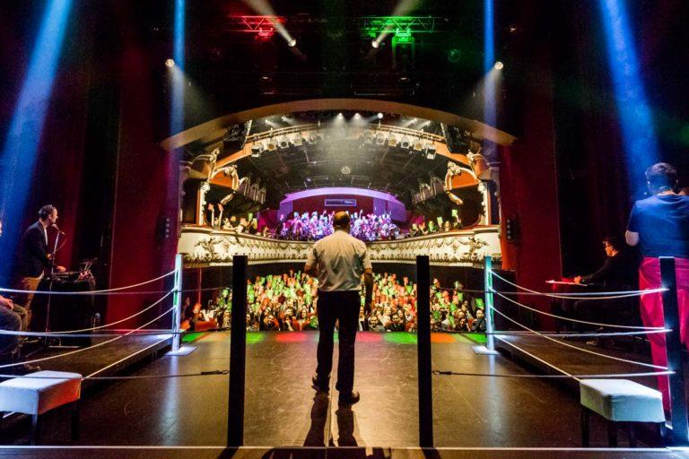 La scène du Casino Théâtre vue de dos lors du Mondial de Catch Impro Professionnel de Genève. L'arbitre, François Briard, est habillé d'un pantalon noir et d'une chemise blanche. Au fond, on voit les spectateurs en train de voter.