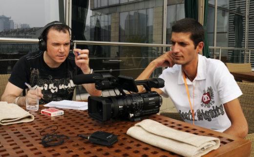 Sarkis Ohanessian, lors de championnats du monde de magie à Pékin, est attablé, un casque sur les oreilles. Il tient un stylo à la main, sur la table sont posés un jeu de cartes, une caméra, un bloc de papier et un micro. A côté de lui se trouve le réalisateur et caméraman Michael Dirani.