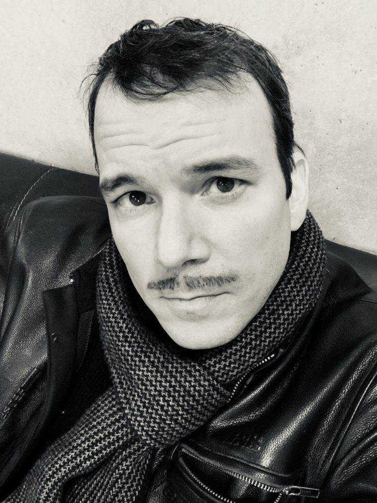 """Photo en noir et blanc de Sarkis Ohanessian sur le tournage de """"Boris""""de Julien Wey. Il a une moustache et regarde l'objectif Il porte une veste en cuir et une écharpe."""