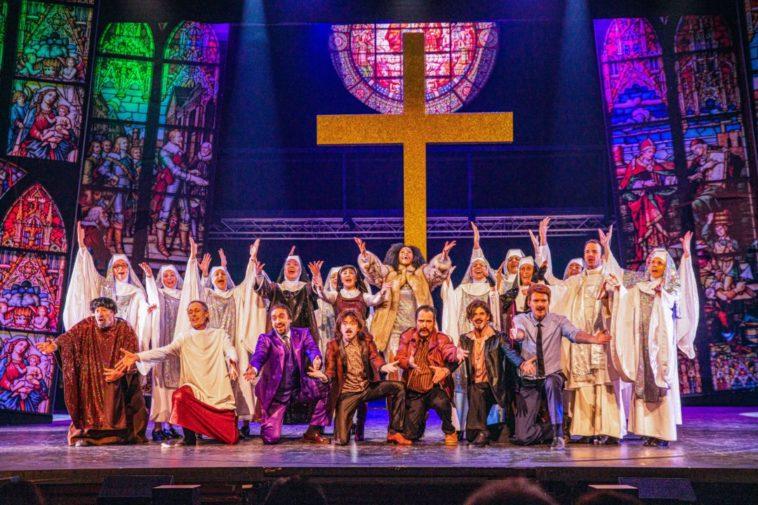 """Saluts finaux du spectacle """"Sister Act"""" au Théâtre Barnabé de Servion. Sarkis Ohanessian, qui interprète Monseigneur O'Hara, est en toge blanche . Il a les mains levées et chante, entouré de tous les comédiens de la troupe."""