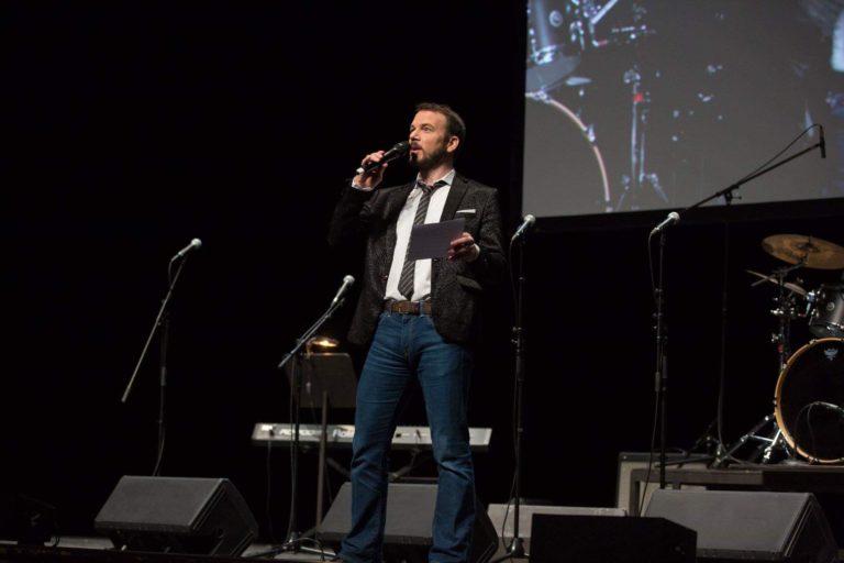 Sarkis Ohanessian est en train de présenter les Promotions Citoyennes de la Ville de Genève sur la scène du Théâtre du Léman. Il porte un jean bleu, une chemise blanche, une veste de costume noire légèrement zébrée et une cravate noire rayée de lignes blanches. Il tient dans sa main droite son micro et dans sa main gauche des fiches.