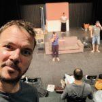 """Selfie de Sarkis Ohanessian en répétition de """"Stationnement alterné"""" de Ray Cooney avec derrière lui la scène du Théâtre le Douze Dix-huit. Sarkis porte un t-shirt gris et on aperçoit derrière Laurence Morisod, Christian Baumann et Julie Depriet."""