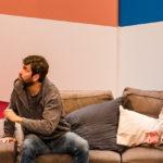 """Sarkis Ohanessian est sur la scène du théâtre le Douze Dix-huit dans """"stationnement alterné"""" de Ray Cooney. Il est assis sur un canapé de Laurent Baier, debout et Christian Baumann, assis. Il porte un jean bleu, une chemise grise et une veste grise."""