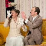 """Sarkis Ohanessian est sur la scène du Théâtre Le Caveau. Il joue """"Thé à la menthe ou t'es citron"""" de Patrick Haudecoeur. Il est assis sur un canapé jaune aux côté de Julie Despriet. Il porte des lunettes rondes et une moustache. Il est vêtu d'un costume gris."""