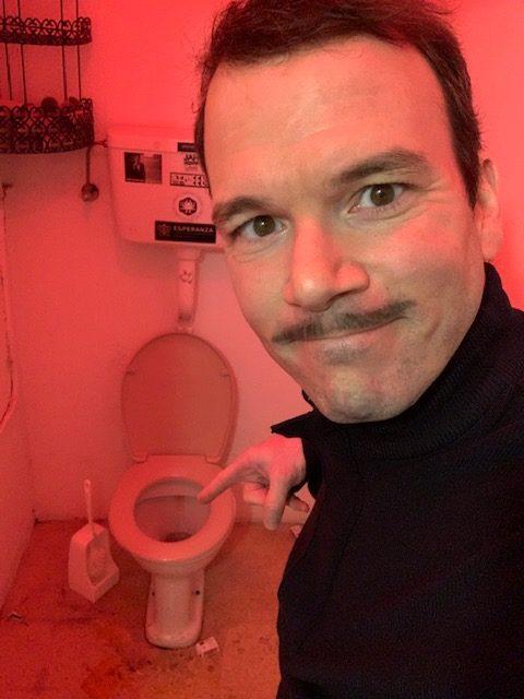 Sarkis Ohanessian, dans le rôle de Boris, porte une moustache. Il montre du doigt la cuvette des toilettes.