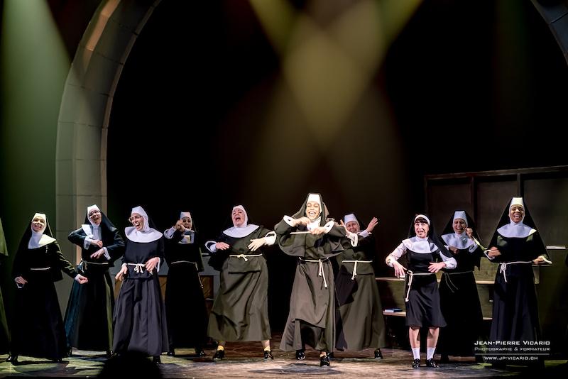 Les nonnes de Sister Act au théâtre Barnabé de Servion chantent et dansent sur la scène. Elles sont toutes habillées de soutanes noires.