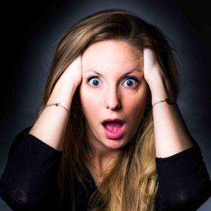 Portrait couleur d'une jeune fille qui a l'air abasourdie. Elle se tient la tête dans les mains, écarquille les yeux et ouvre la bouche. Elle porte des bracelets aux poignets.