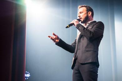 Photo couleur de Sarkis Ohanessian en train de présenter un spectacle. Il est vêtu d'un costume noir trois pièces et parle dans le micro. Il porte une barbe bien taillée.