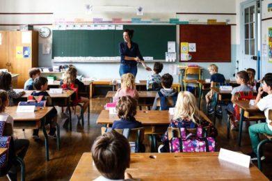 Photo couleur d'une salle de classe avec des enfants aux pupitres. Au fond vers le tableau, une enseignante en action.
