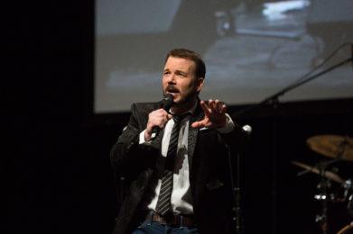 Sarkis Ohanessian est en train de parler dans le micro lors de la présentation des Promotions Citoyennes de la Ville de Genève. Il porte un jean bleu, une chemise blanche, une cravate rayée et une veste de costume noire